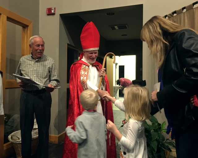 "Young parishioners shake hands Dec. 2 with an actor portraying St. Nicholas, the namesake of their church. St. Nicholas Catholic Church in Santa Claus, Ind., hosted the visit from ""St. Nick"" ahead of the saint's feast day Dec. 6. (CNS/Katie Rutter)"