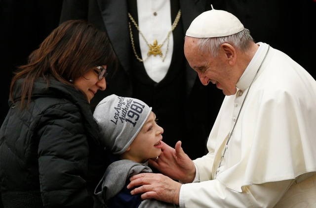 Pope Francis greets a child as he meets the disabled during his general audience in Paul VI hall at the Vatican Dec. 6. (CNS/Paul Haring)